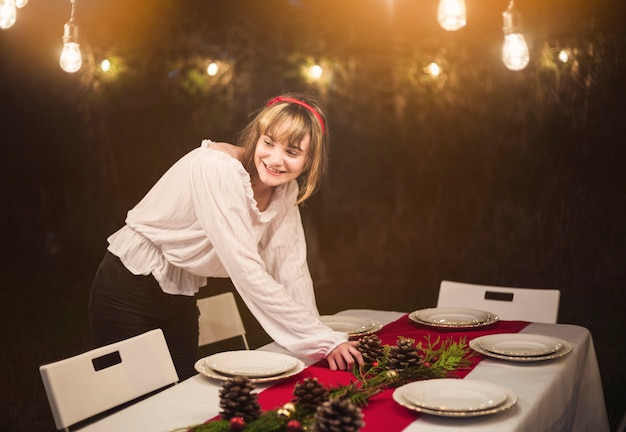 Young woman setting the table for christmas dinner