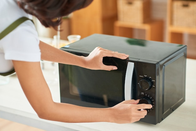 有機石鹸やレーを作るためにオレンジとレモンのスライスを乾燥させるときに電子レンジに時間を設定する若い女性