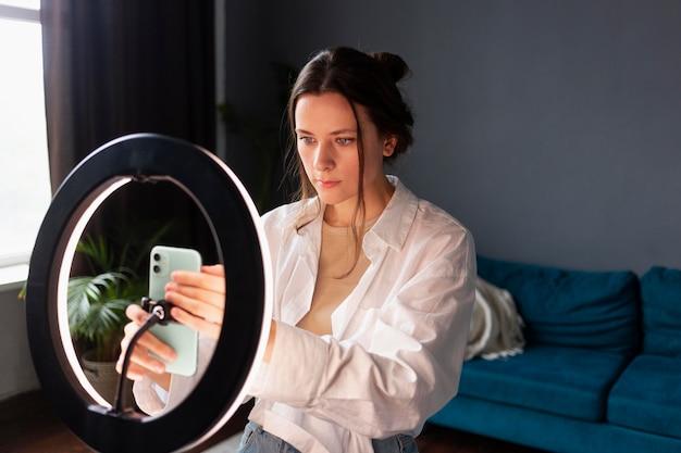 彼女のvlogのための機器をセットアップする若い女性