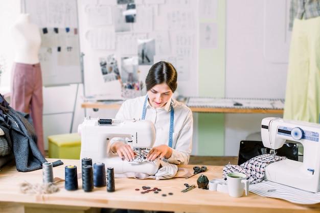 Молодая женщина шить с швейной машиной на студии пока сидящ на ее месте службы. модельер тщательно создает новые модные стили. портниха делает одежду