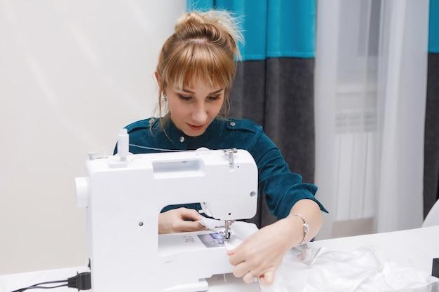 若い女性は、ワークショップでミシンで縫います。