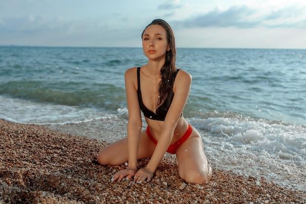 ビーチで彼女の膝の上に座ってセクシーな若い女性