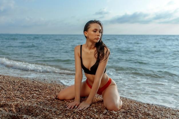 Сексуальная молодая женщина сидит на коленях на пляже