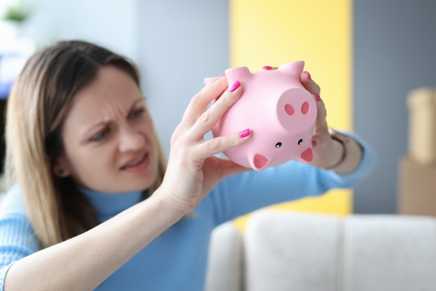 Young woman shaking piggy bank with money
