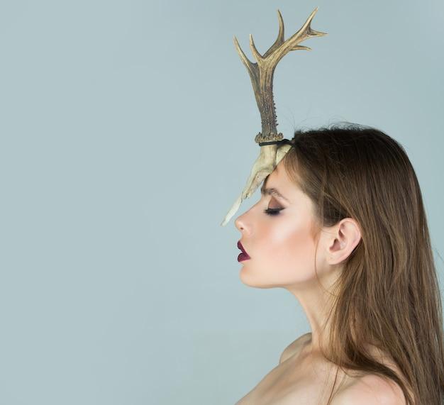 젊은 여자 무당이 그녀의 머리에 동물의 뿔을 가지고 떠오른다