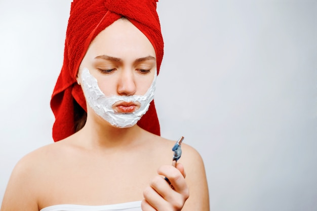 Young woman shaves her beard with a razor, girl does not want to shave her beard emotional gender role