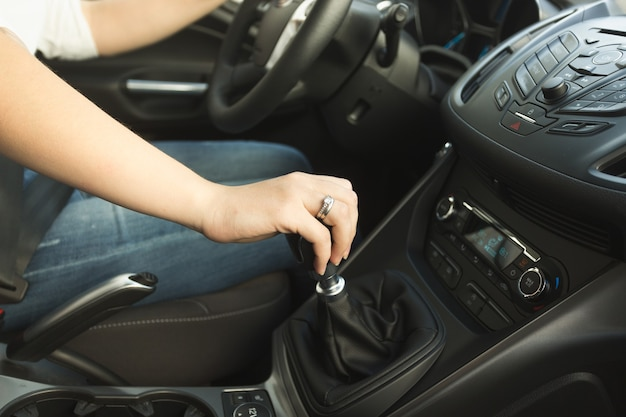 Young woman shifting gearbox in car