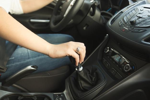車の中でギアボックスをシフトする若い女性