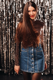 A young woman in a shiny jacket posing over silver tinsel curtain