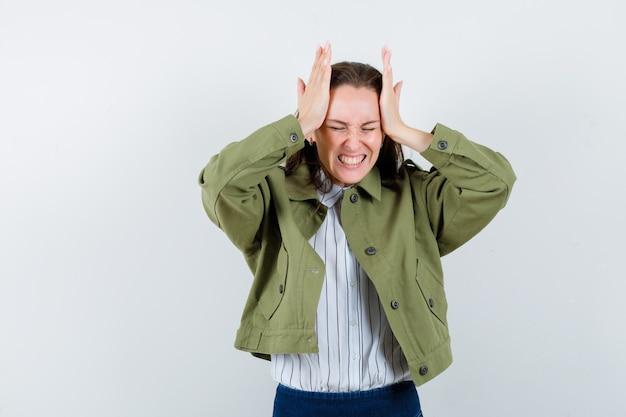 Giovane donna in camicia, giacca che stringe la testa con le mani e sembra dispiaciuta, vista frontale.