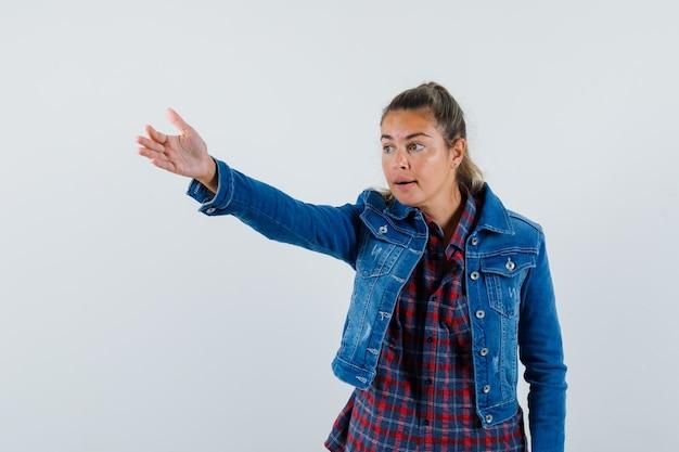 Giovane donna in camicia, giacca che dà istruzioni allungando il braccio, vista frontale.