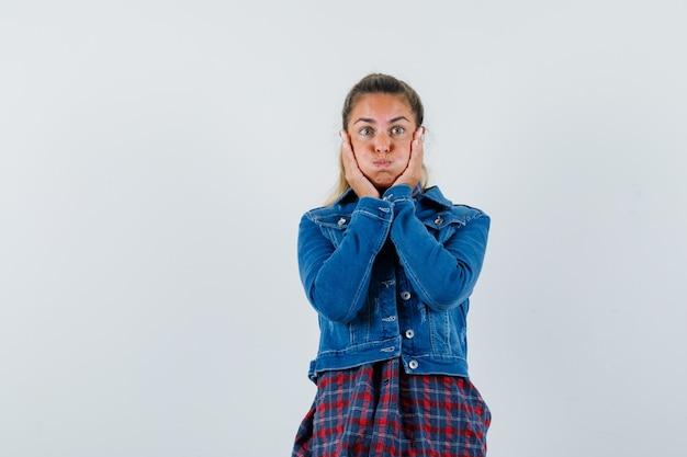 Giovane donna in camicia, giacca tenendo le mani sulle guance soffiate e guardando impotente, vista frontale.