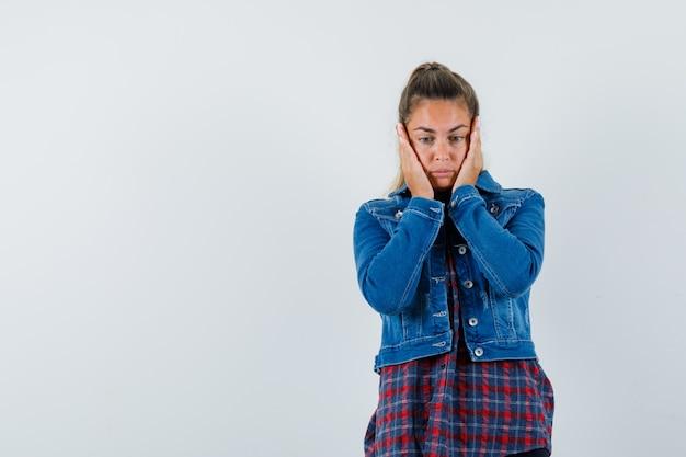 Giovane donna in camicia, giacca tenendo le mani sulle guance e guardando impotente, vista frontale.