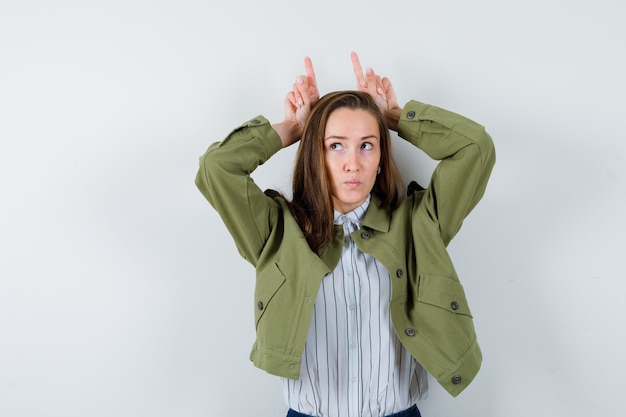Young woman in shirt, jacket keeping fingers over head as bull horns and looking pensive , front view.