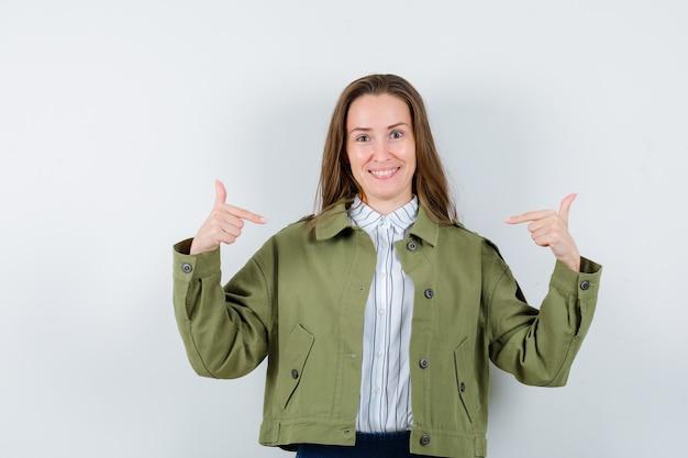 Giovane donna in camicia, giacca che indica se stessa e sembra allegra, vista frontale.
