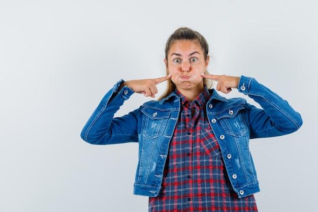 Giovane donna in camicia, giacca premendo le dita sulle guance soffiate e guardando divertente, vista frontale.