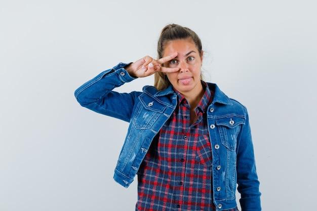 Giovane donna in camicia, giacca che mostra il segno v sull'occhio e sembra felice, vista frontale.