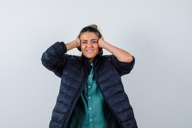 Giovane donna in camicia, piumino che stringe la testa con le mani e sembra felice, vista frontale.