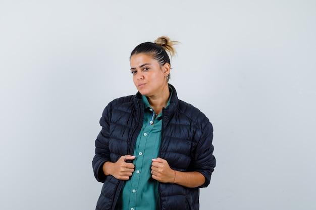 Giovane donna in camicia, piumino in posa in piedi e guardando fiducioso, vista frontale.