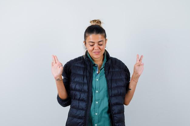 Giovane donna in camicia, piumino che mostra gesto di resa mentre chiude gli occhi e si vergogna, vista frontale.