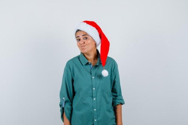 Giovane donna in camicia, cappello da babbo natale che increspa le labbra e guarda perplesso, vista frontale.