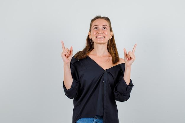 Giovane donna in camicia, pantaloncini, occhiali rivolti verso l'alto con il gesto della pistola e guardando allegro