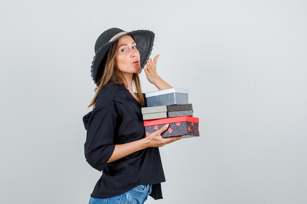 Young woman in shirt, shorts, hat holding gift boxes while sending air kiss .