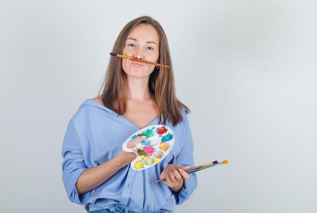Giovane donna in camicia, pantaloncini tenendo il pennello e la tavolozza e guardando divertente