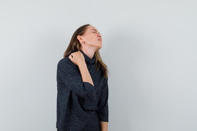 Giovane donna in camicia che soffre di dolore al collo e sembra affaticata
