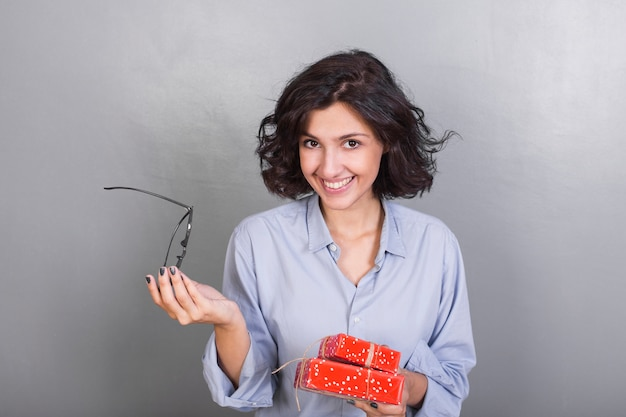 Young woman in shirt with gift boxes