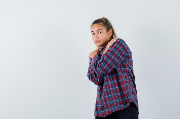 チェックのシャツで寒さから震え、疲れ果てているように見える若い女性