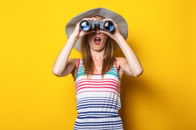 Young woman in shock in surprise with a hat and a striped dress looks in surprise with binoculars on a yellow space.
