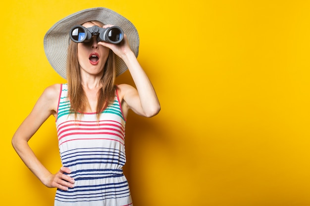 Young woman in shock in surprise with a hat and a striped dress looks in surprise with binoculars on a yellow space