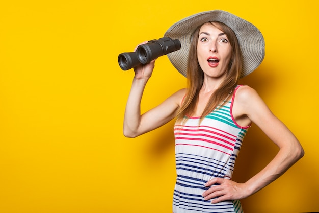 Young woman in shock, surprised, in a hat and striped dress holds binoculars on a yellow space.