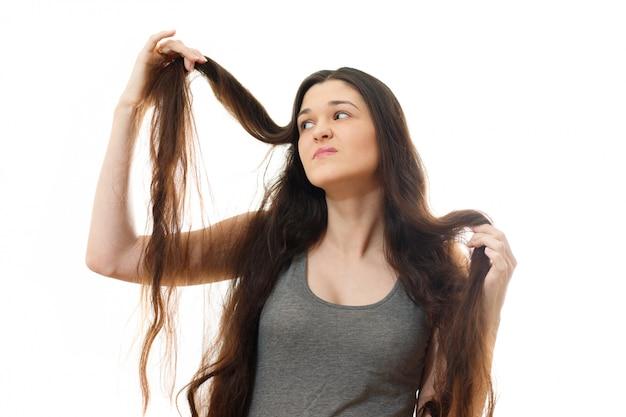 Молодая женщина шокирована проблемой секущихся волос