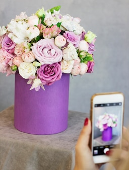 Young woman shooting beautiful floral bouquet in purple box