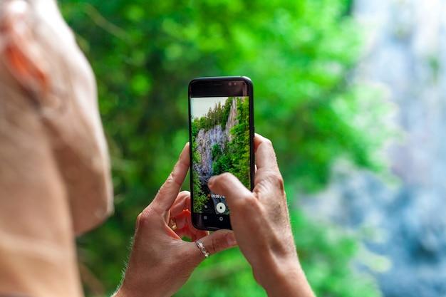 若い女性が自然のビデオをスマートフォンで撮影します。