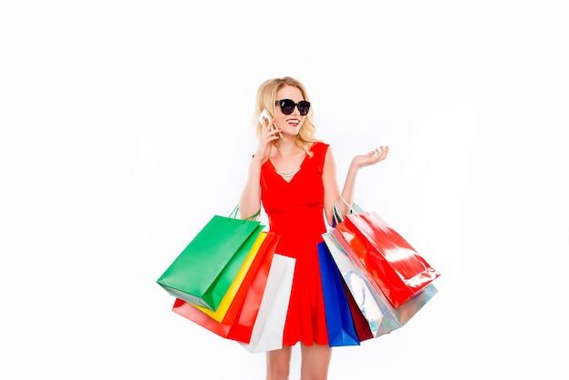 電話で話している色のペーパーバッグと買い物中毒の若い女性