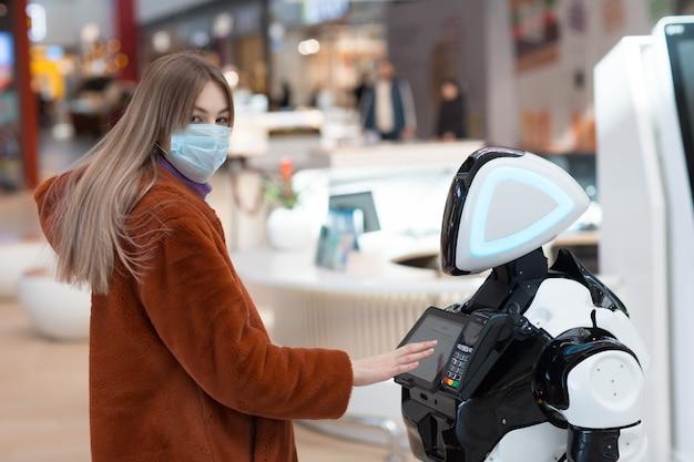 Покупатель молодой женщины и робот-консультант в магазине