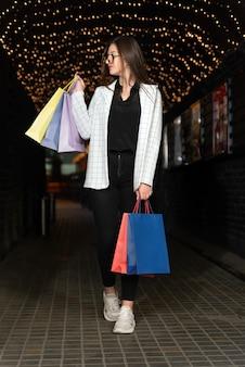 若い女性の買い物客は、夜の街灯を背景に色とりどりの買い物袋を持っています。垂直フレーム。