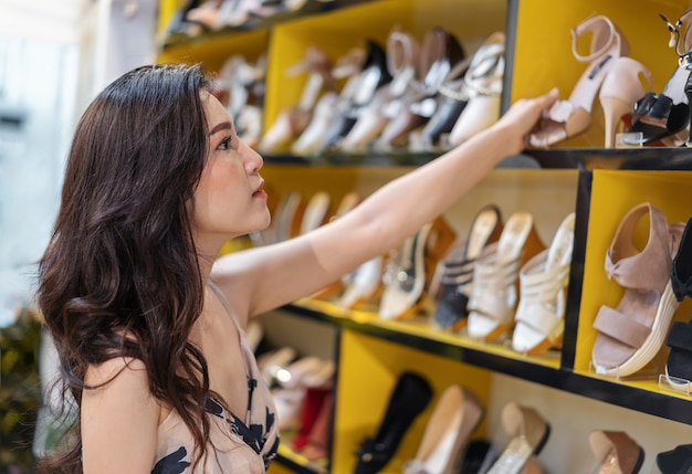 Young woman shopping high heel shoes in shop