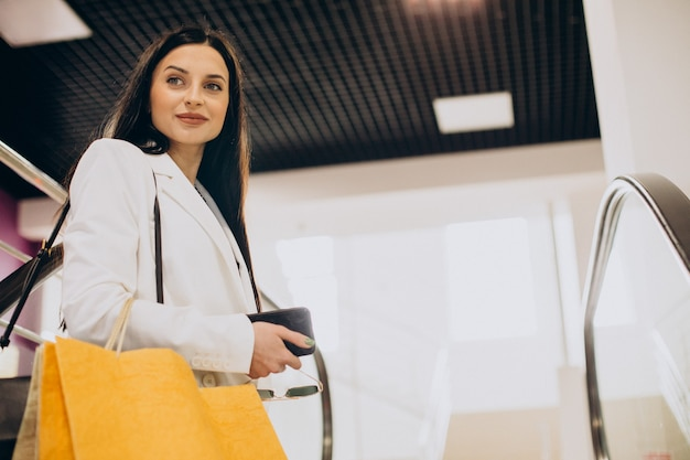 Young woman at shopping mall going up on escalator