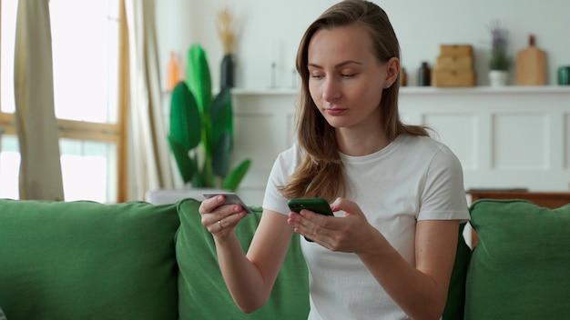 自宅のソファに座ってクレジットカードとスマートフォンでオンラインショッピングをする若い女性。