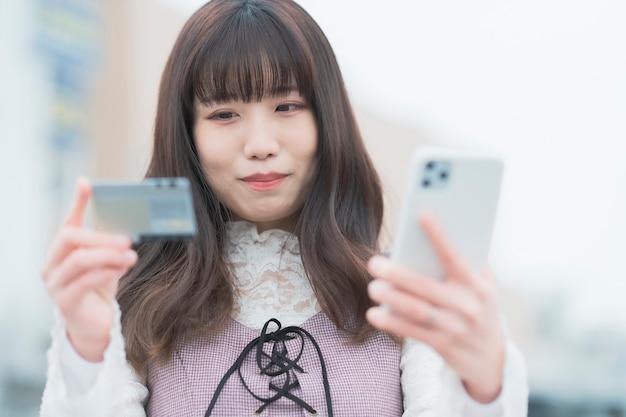 신용 카드와 스마트 폰 온라인 쇼핑하는 젊은 여자