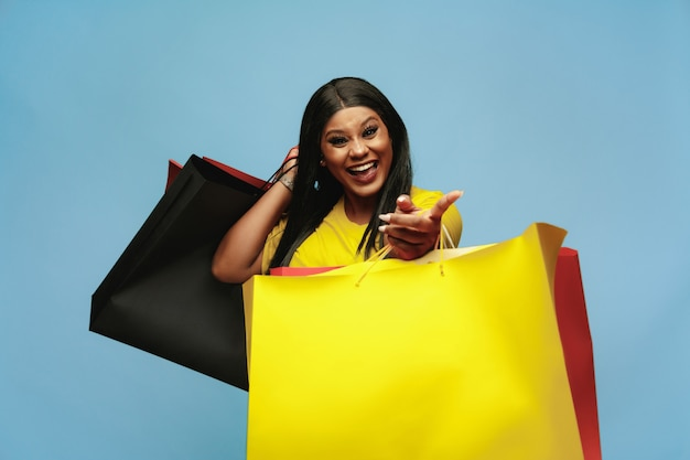 Young woman shopping with colorful packs on blue wall