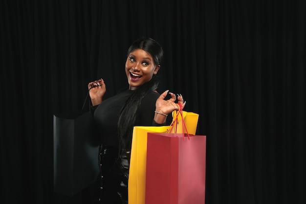 검은 벽에 화려한 팩과 함께 쇼핑하는 젊은 여자
