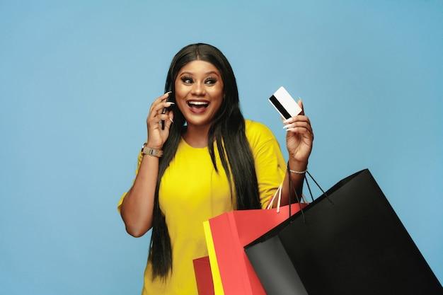 青い壁にカラフルなパックで買い物をする若い女性