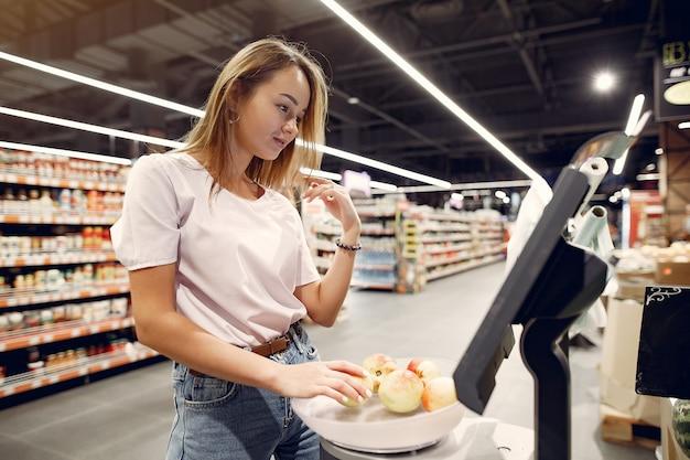 Shoppong молодой женщины в супермаркете