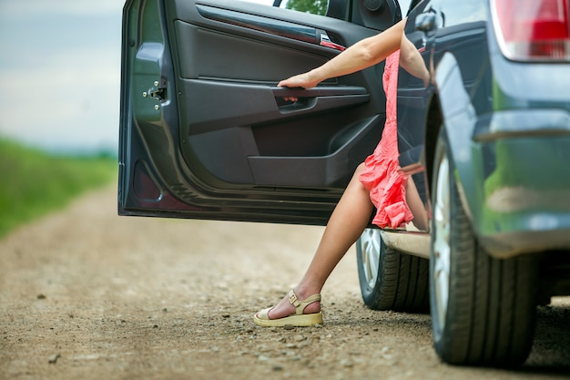 Young woman in short dress getting out car with open door on sunny blurred rural road