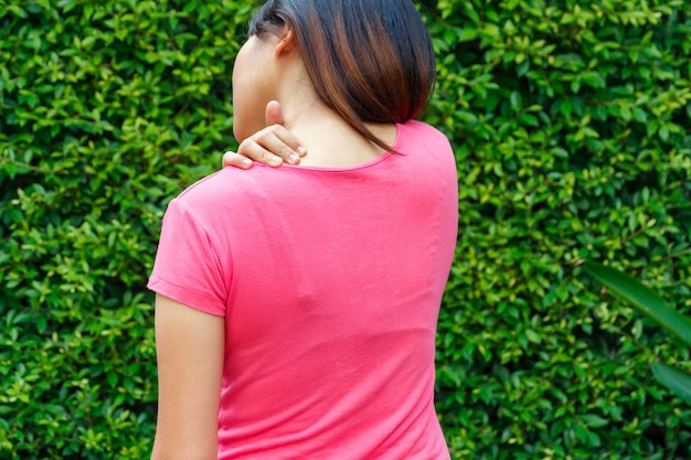 Young woman shoulder or joint pain in public park.